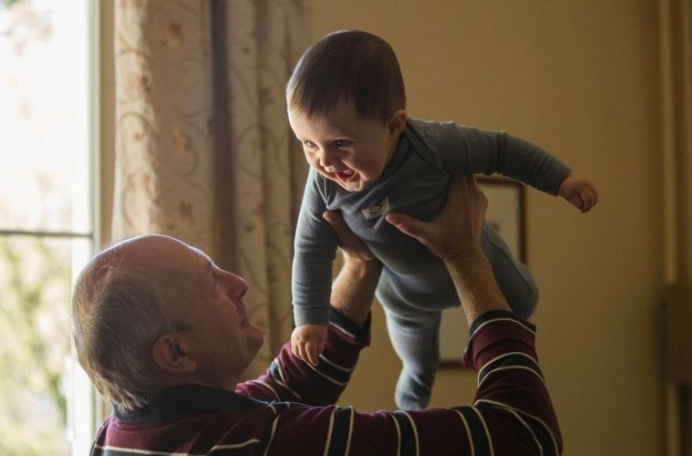 grandfather holding smiling baby in the air
