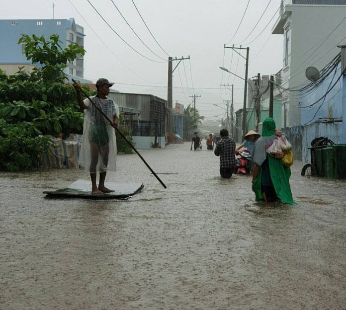 A resident paddles along a flooded road.