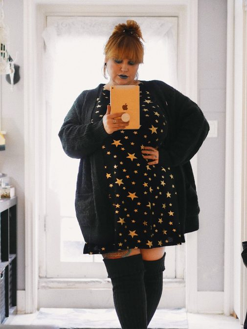 Margot Meanie poses in plus size outfit featuring a black sweater and star print dress