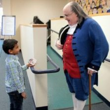 Ben Franklin impersonator talks with a young event attendee