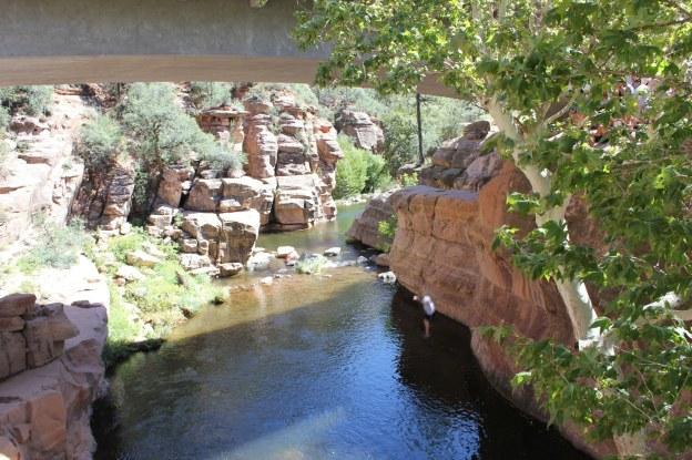 Adventurers cliff-jump into pool of water at Slide Rock Park near Flagstaff, Arizona