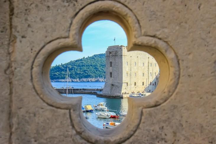 Peering through a hole in the bridge to Old Port in Dubrovnik, Croatia