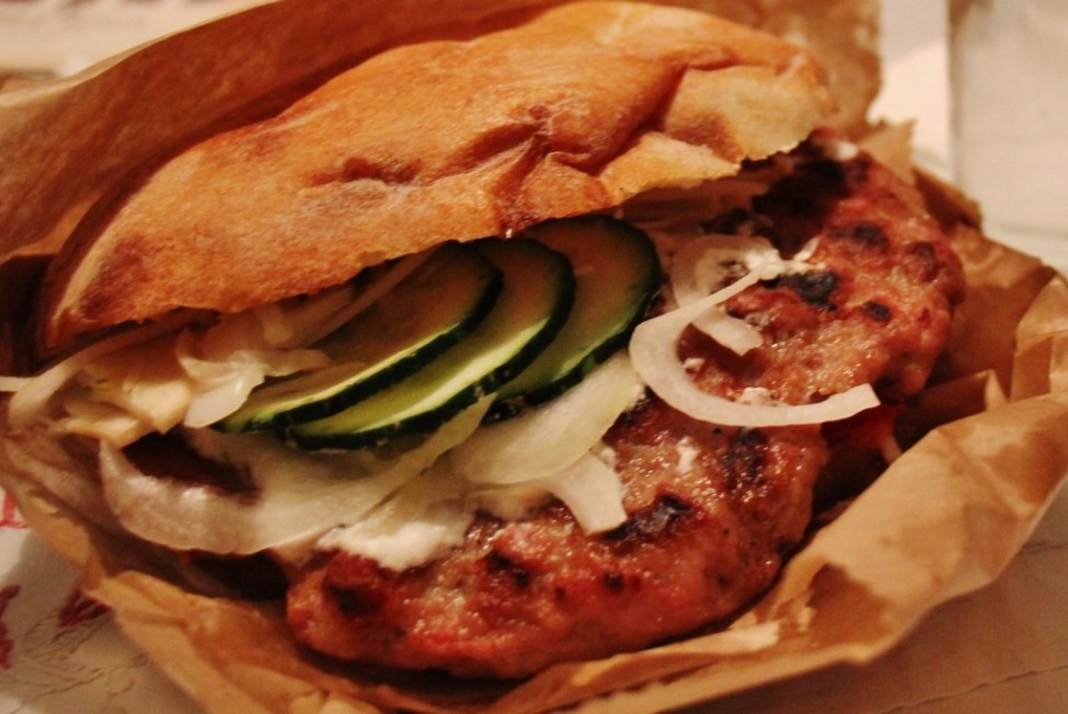 Pljeskavica burger topped with onion and cucumber in Belgrade, Serbia