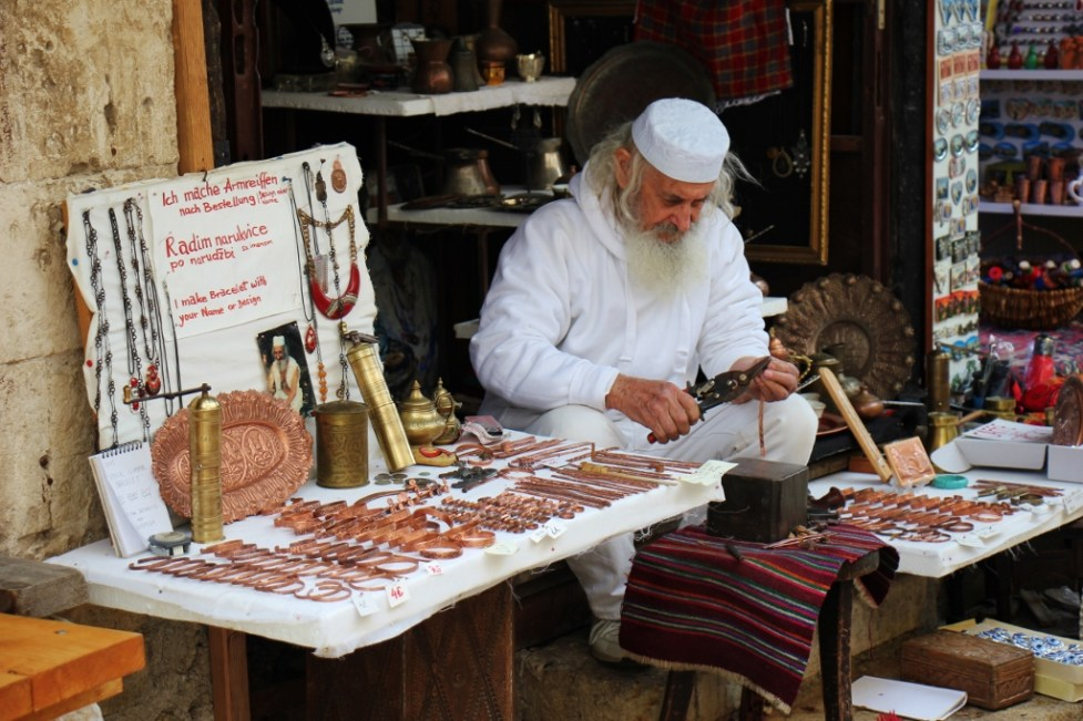 Man uses tools to make copper souvenirs in Mostar, Bosnia-Herzegovina