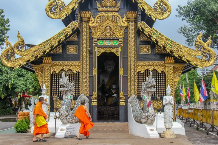 Two monks walking into Wat Inthakhin Sadue Muang Temple in Chiang Mai, Thailand