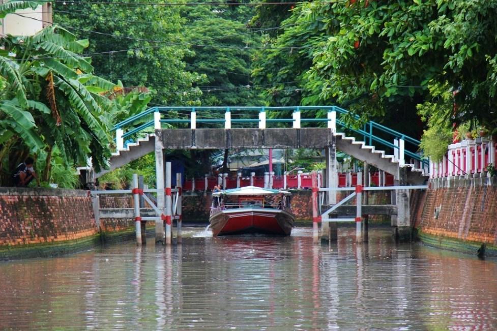 Passenger boat sails under low bridge on Saen Saep Canal (Khlong) in Bangkok, Thailand