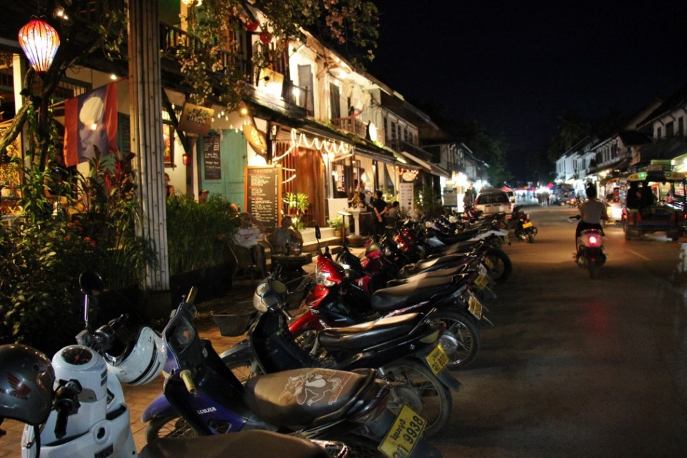 Motor scooters line the street in Luang Prabang, Laos at night