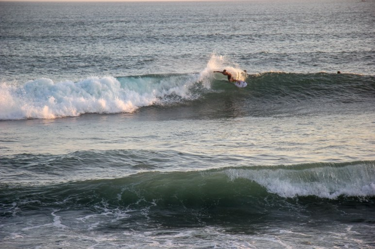 Surfer riding the waves at Echo Beach in Canggu, Bali, Indonesia