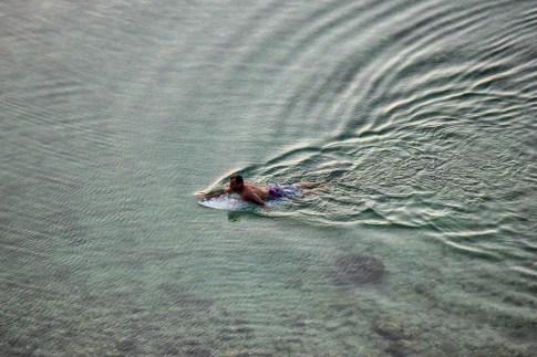 Surfer paddles in making a wake at Uluwatu Beach in Uluwatu, Bali, Indonesia