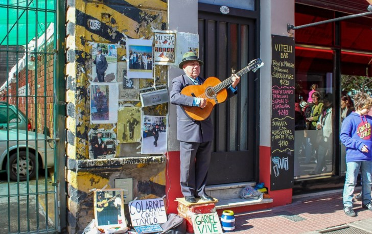 Man sings and plays guitar on Defensa Street in Buenos Aires, Argentina