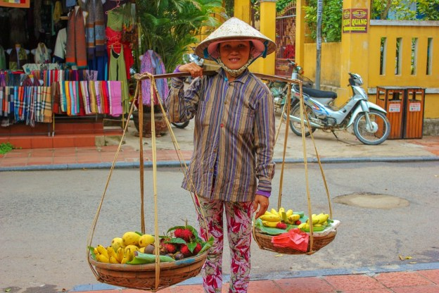 Girl sells produce from baskets in lane in Hoi An, Vietnam