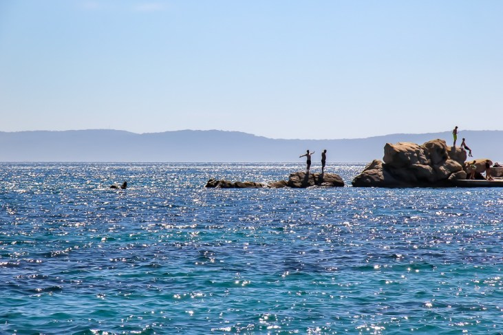 Boys explore the rocks on the western side of Bacvice Beach in Split, Croatia