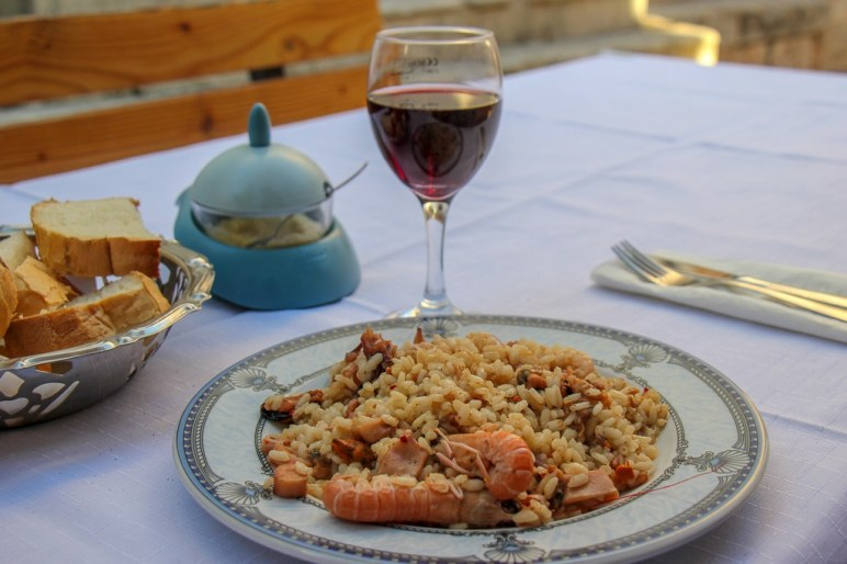 Plate of Seafood Risotto and glass of wine at Junior Restaurant in Hvar, Croatia