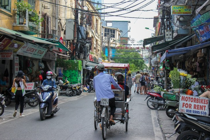 Man pedals cyclo carrying tourists in Hanoi, Vietnam