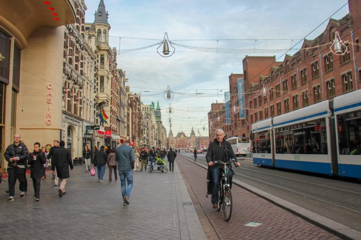 Bikes and people make up the hectic Damrak traffic, Amsterdam, Netherlands