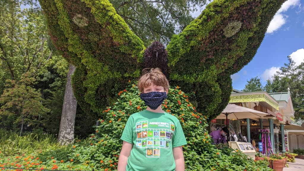 Evan Smith posing in front of a butterfly landscape sculpture at Dollywood