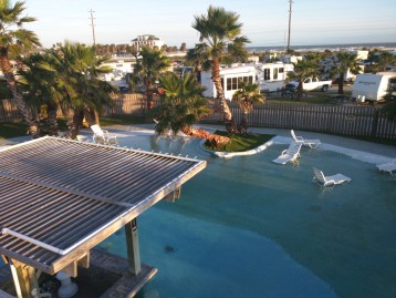 Since everything is up on stilts, you'll need to climb stairs to get to the restrooms about 15 feet above ground. Looking down from the restroom deck over the shallow lounge pool.