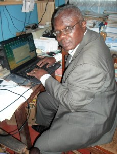 Photo of me in suit and working on a laptop in my home office