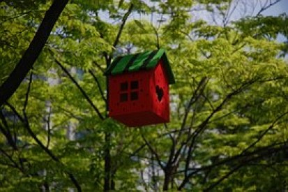 A red bird house with a green roof niched in leafy trees.
