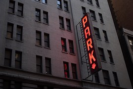 "A red neon vertical sign on a high rise apartment building reading ""Park"""