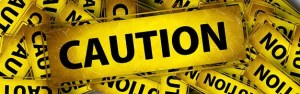"""A large yellow banner among smaller ones with black inscription in bold """"CAUTION"""""""