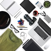 Picture displaying miscellaneous items of camera, T-shirt, iPhone, MacBook Pro, glasses, pencils, etc.