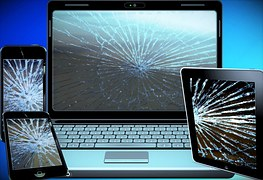 A laptop and three mobile phones with broken screens to signify electronic scrap to be recycled