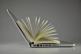 A laptop with a book opened on it to signify online learning