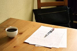 Pages of text on a text with a pen and a cup of coffee for proofreading