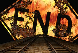 The word END written in black at the end of railway tracks where there is some sort of sunset