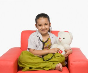 Girl examining a teddy bear with a stethoscope