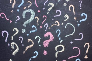 Multicolored question marks are painted with chalk