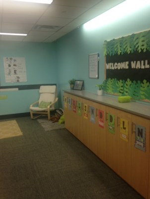 This nook showcases the welcome wall in a PreK 3 room, which reflects what the class is studying. Also featured, the student's cubbies and a quiet reading corner.