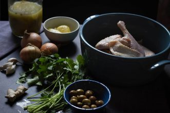 Ingredients of a moroccan chicken tagine (chicken legs, onions, preserved lemons, ginger, garlic, olives, cilantro)