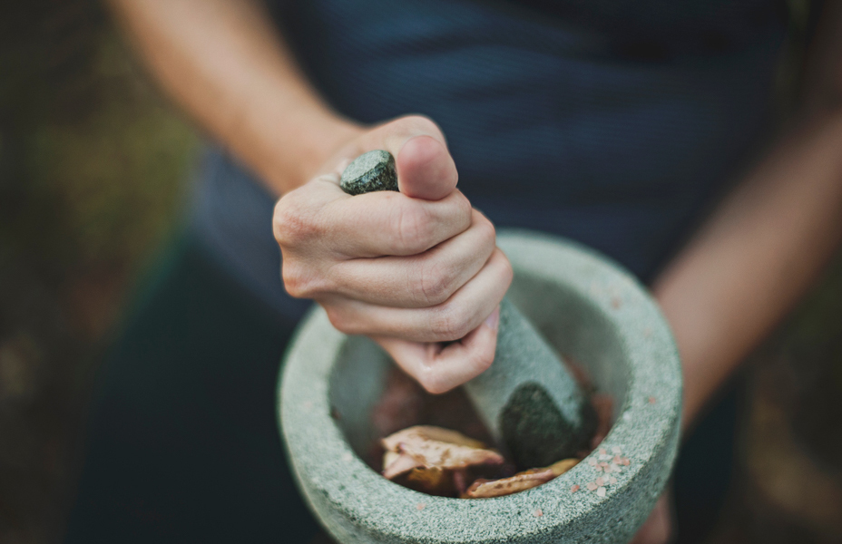 A women hand pesting herbs in a stone mortar
