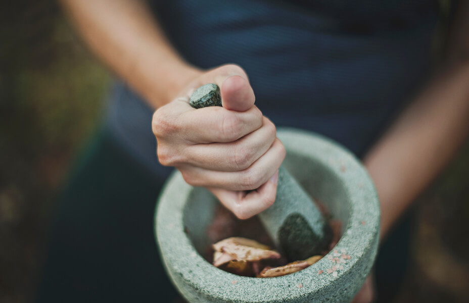 A woman hand pesting spices and herbs in a mortar