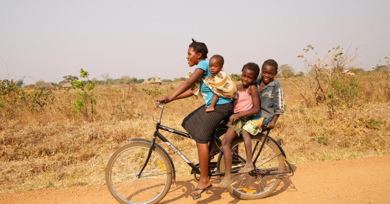 women riding bike with kids