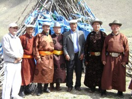 Local men in front of the oboo. Many Mongols still wear traditional Mongol costume - a requirement for attending an oboo worship ceremony and any other national festival.