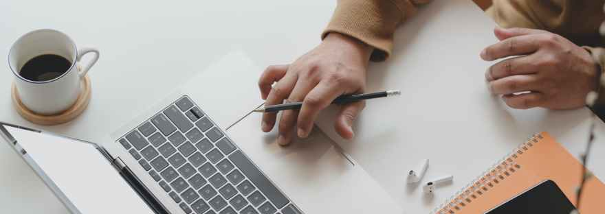 person holding black pen while using laptop