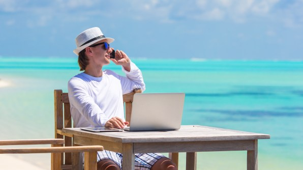 Young man with laptop and cell phone on tropical beach