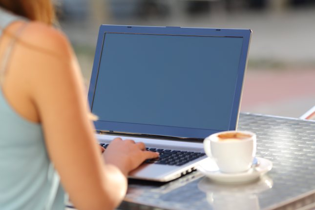 Closeup of a girl typing on a laptop and showing screen in a restaurant terrace