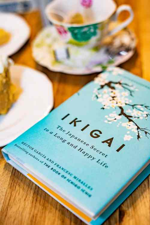 Ikigai hardcover book in the foreground with a teacup in the background. The teacup has a flowered design.