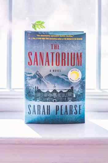 Hardcover copy of the book The Sanatorium on a windowsill.
