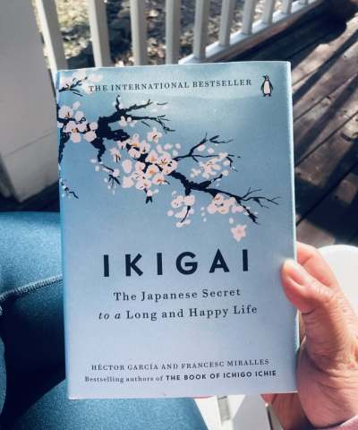 hand holding hardcover copy of the book Ikigai