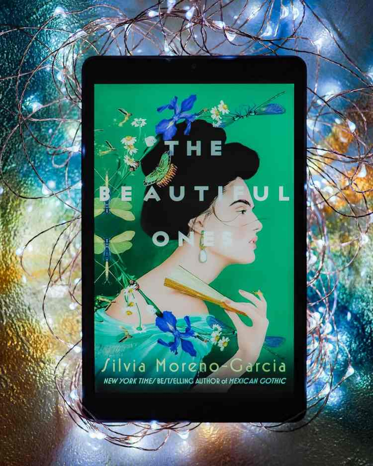 Tablet showing the cover of The Beautiful Ones by Silvia Moreno-Garcia on the screen. The tablet is laying in an iridescent bowl that is filled with sparkling LED lights.