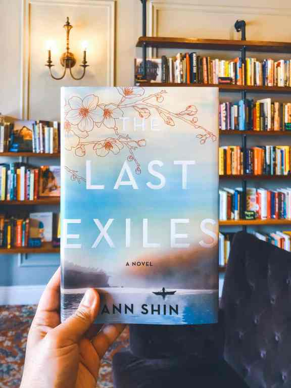 A hand is holding up the book The Last Exiles by Ann Shin. There are bookshelves in the background.