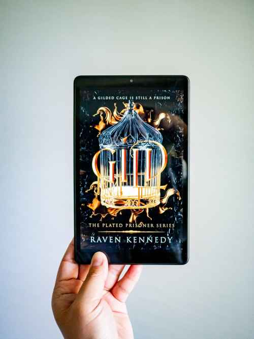 A hand is holding a tablet which has the book cover for Gild by Raven Kennedy on its screen.