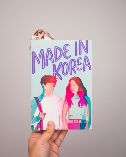 A hand is holding the book Made in Korea by Sarah Suk.