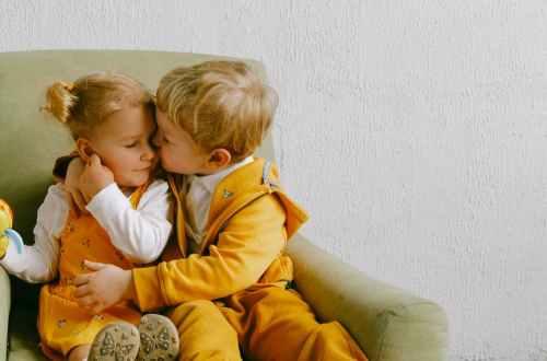 cute children cuddling in armchair at home