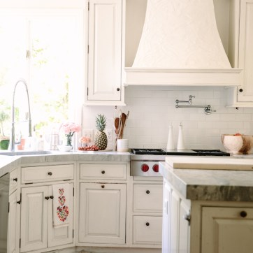 The chef-style kitchen features honed white marble countertops and fresh white cabinetry.